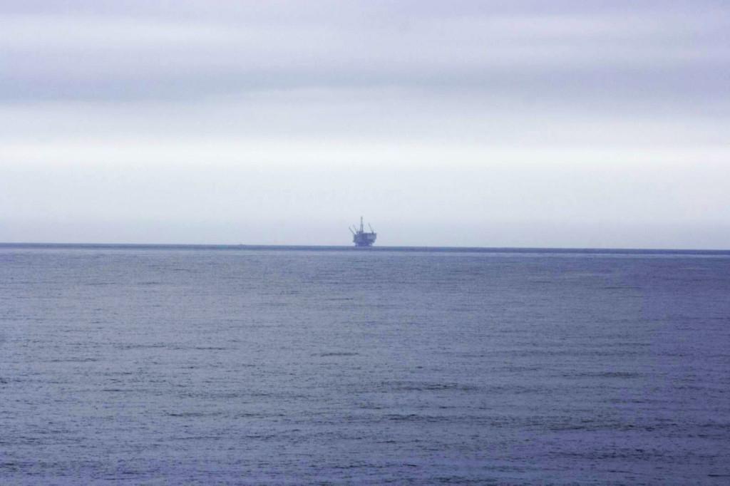 Вдали далеко-далеко от берега в Тихом океане виднеется нефтяная вышка